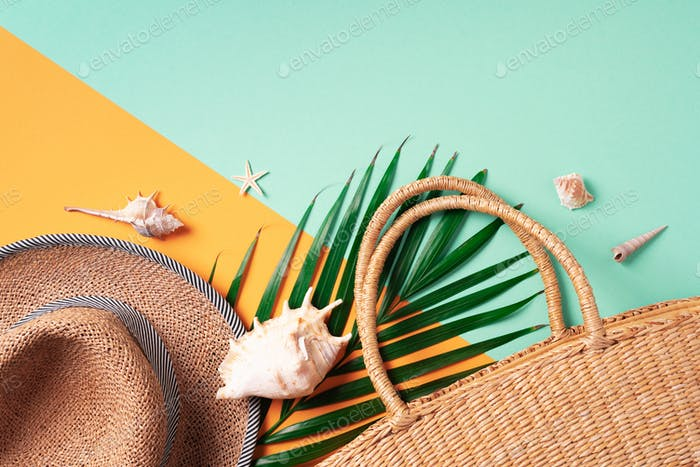 Summer travel concept with women straw bag, hat, palm leaves, shells on trendy yellow and green