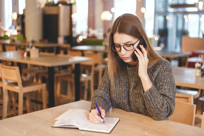 Young woman accountant talking on cell phone
