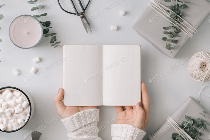 Girl's hands hold an blank notebook