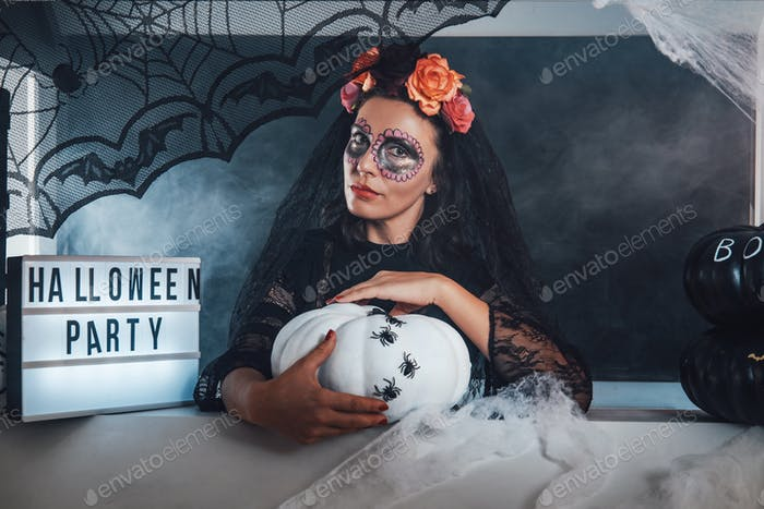 Beautiful witch with floral wreath in black clothing in studio