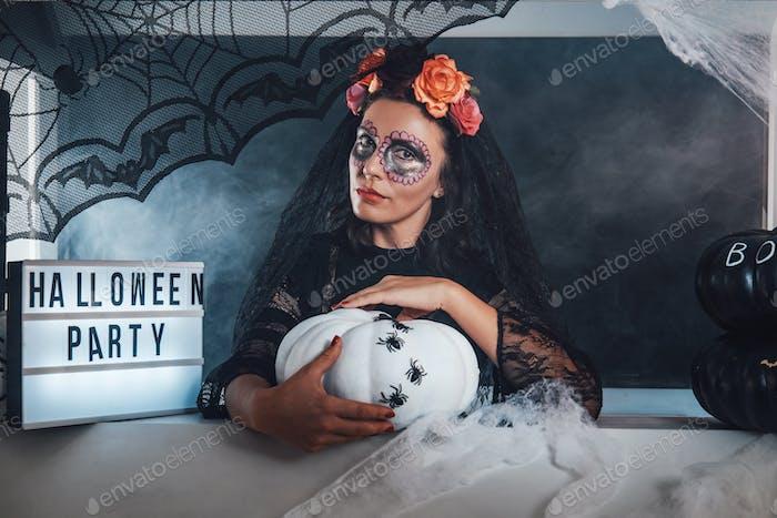 Schöne Hexe mit Blumenkranz in schwarzer Kleidung im Studio