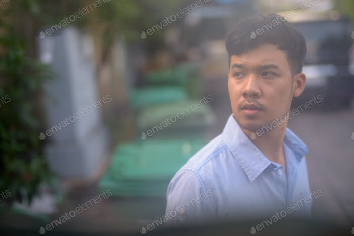 Young Asian businessman thinking in the streets outdoors