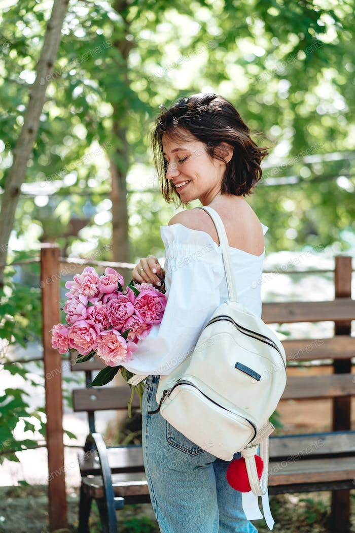 Young woman with a bouquet of pink peonies