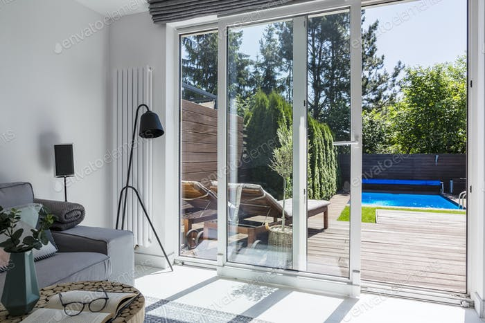 Flowers on table next to grey sofa and black lamp in living room