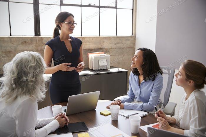 Female manager in glasses addressing businesswomen in meeting