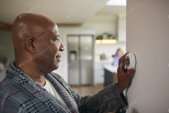 Mature Man Turning Control Dial On Digital Central Heating Thermostat At Home