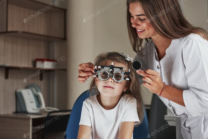 Looking at board. Little girl in glasses sitting in clinic and having her eyes tested