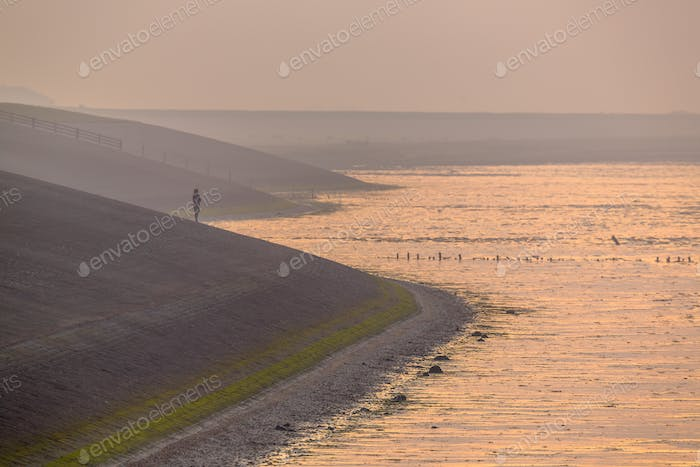 Person watching sunset from Sea dike in orange haze