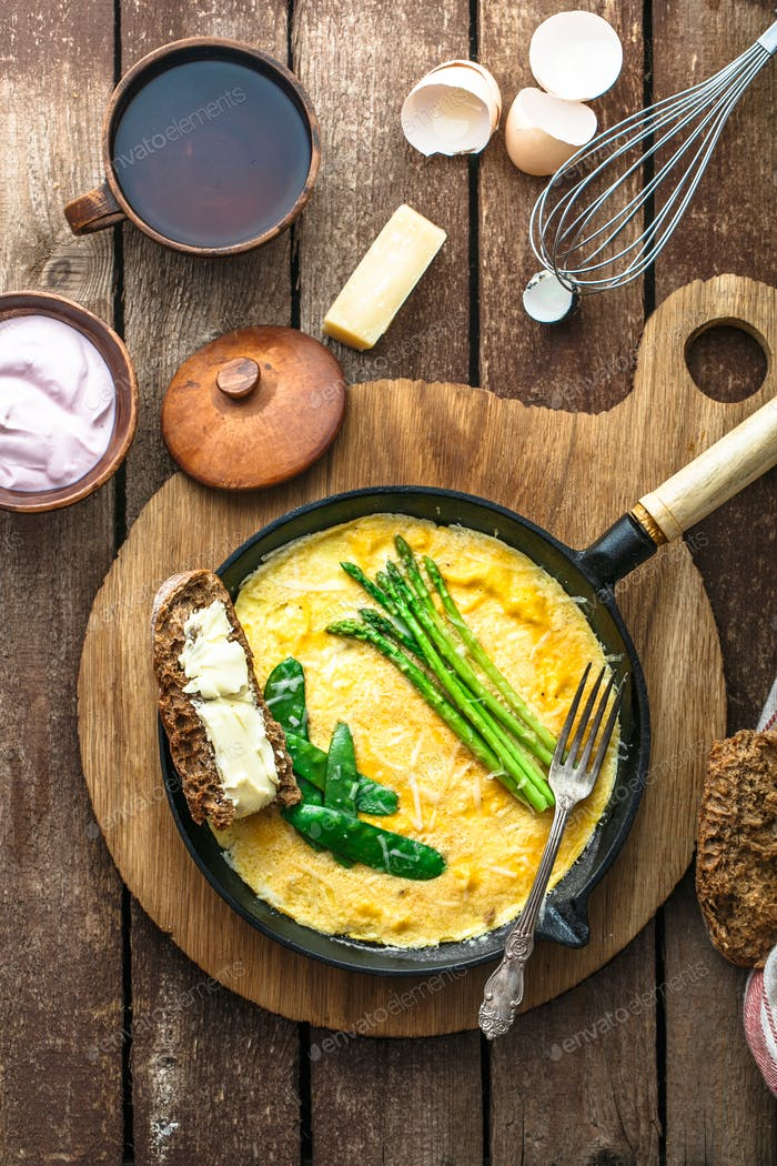 Omelet with green asparagus, pea on frying pan, top view, rustic style