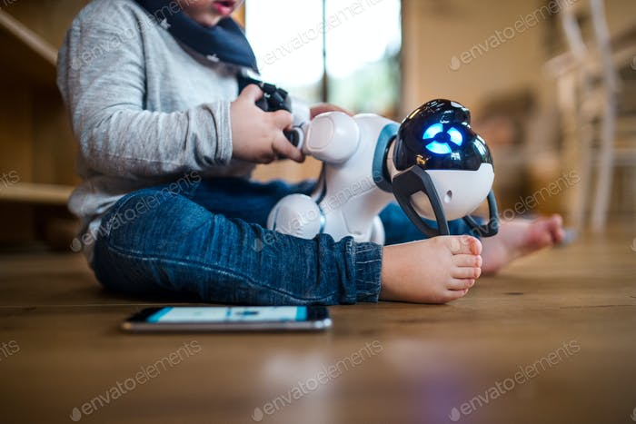 A midsection of toddler boy sitting indoors at home, playing with robotic dog.