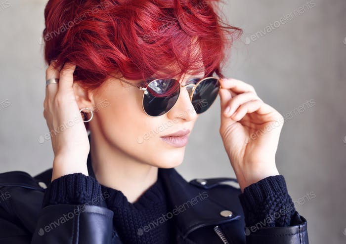 Portrait of a beautiful young red-haired woman wearing sunglasse