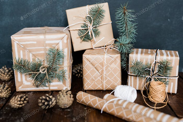 Giftboxes with conifer on top, rolled paper, threads for binding and pinecones