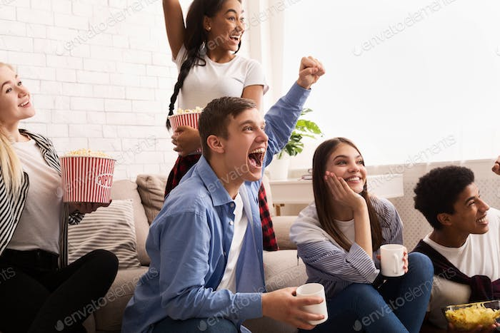 Emotional teenagers watching football on tv and cheering