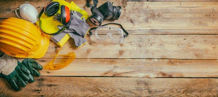 Bausicherheit Schutzmütze, Kopfhörer, Handschuhe und Brille auf hölzernem Hintergrund