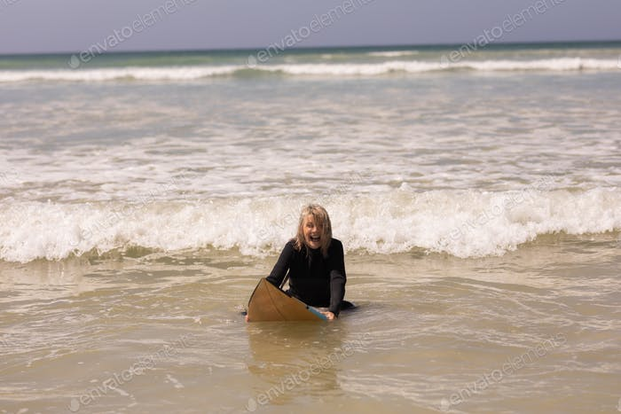 Front view of happy senior female surfer with surfboard surfing in sea on a sunny day