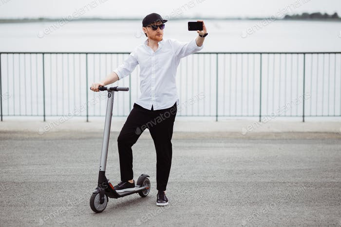 Modern man in stylish outfit making selfie while standing at the street with electric scooter