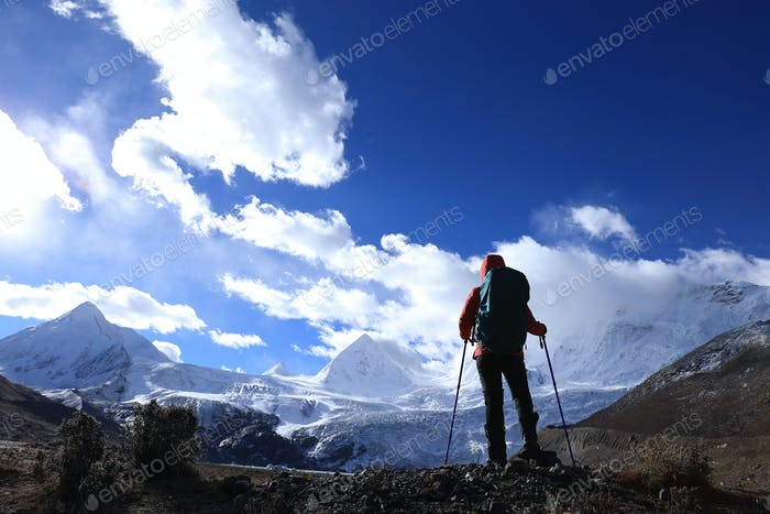 Woman hiker hiking  in winter mountains