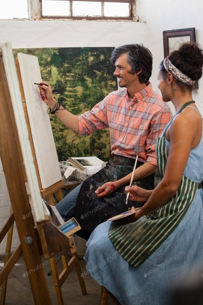 Man assisting woman to sketch