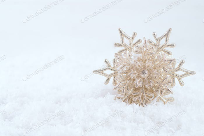 Gold Christmas decoration. Beautiful snowflake on snow background. Winter holidays concept