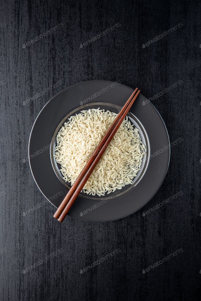 Uncooked indian long rice on plate and chopsticks.