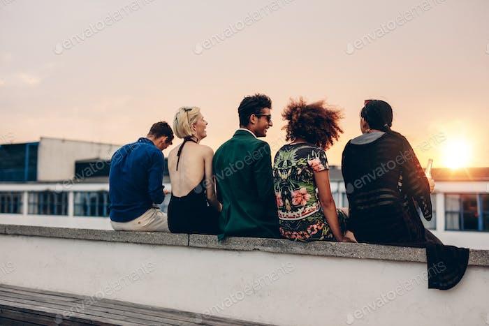 Junge Freunde entspannen auf der Terrasse während des Sonnenuntergangs