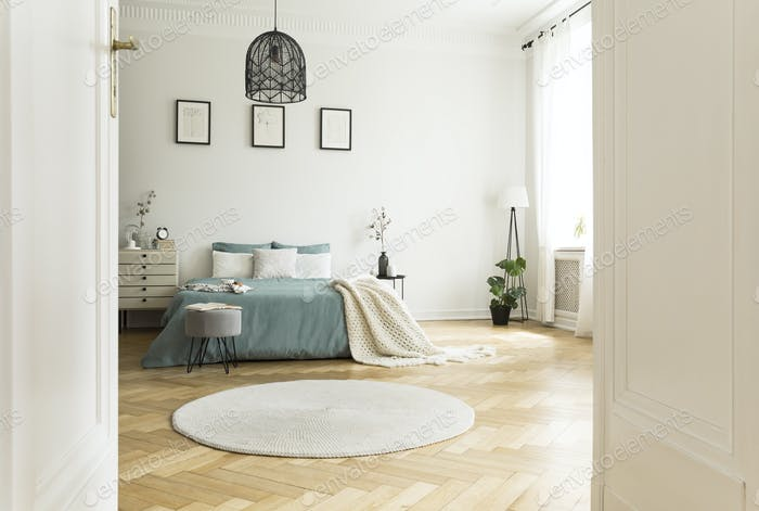 White round rug in spacious bedroom interior with green bed unde