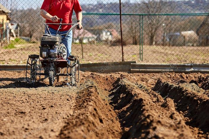 Mann, der im Garten mit Gartenfräse arbeitet.