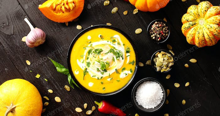 Yellow fresh pumpkin soup surrounded by spices and seeds