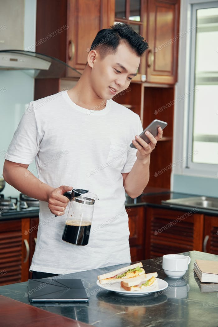 Man using phone and making breakfast