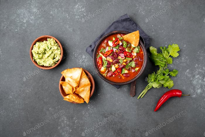 Mexican black bean soup with tomato, avocado and totopos. Gray background, top view