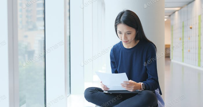 Student studying on paper note inside university campus