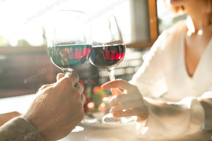 Hands of two young amorous dates clinking with glasses of red wine