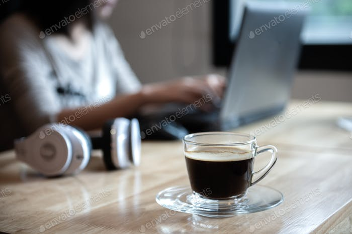 Coffee cup on the front desk with people using laptop.