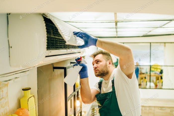 Repairman in uniform cleans the air conditioner