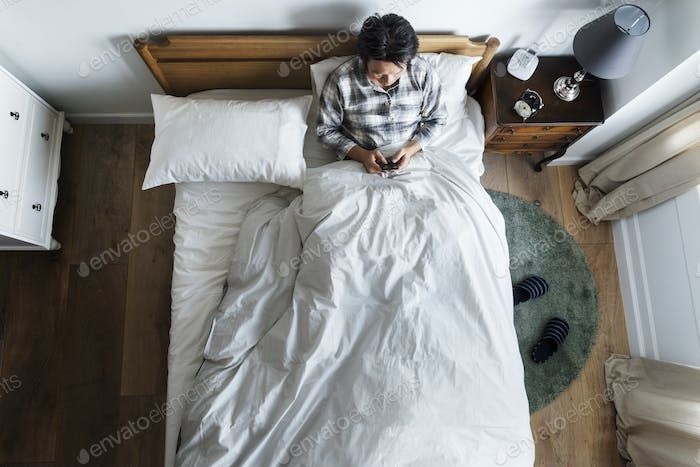 Asian ethnicity guy using phone on the bed