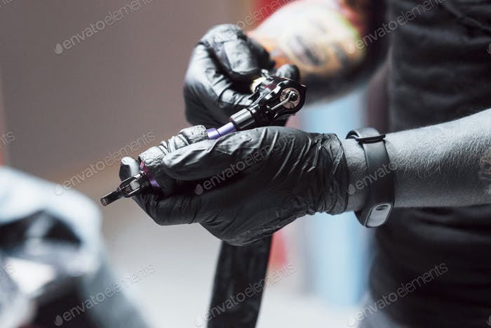 Artist holding tattoo machine in his studio, he is ready to accept the client