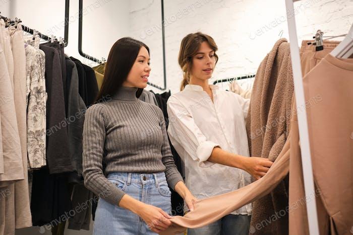 Junge Designer zeigt Kleidung aus der neuen Sammlung zu attraktiven asiatischen Mädchen in Bekleidungsgeschäft