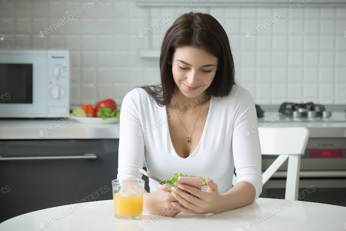 Portrait of smiling woman with smartphone having healthy lunch