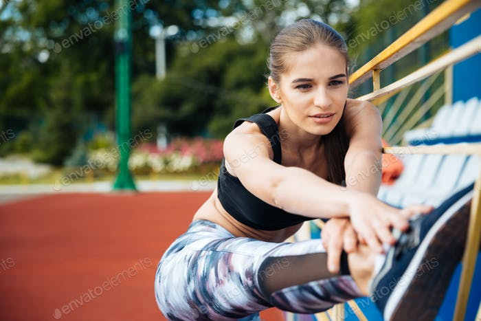 Woman athlete stretching legs and working out on stadium
