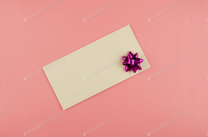 Flat lay view at blank greeting card with bow on pink background. Space for text