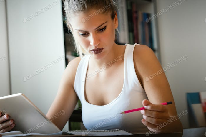 Pretty young college student studying, preparing for exam