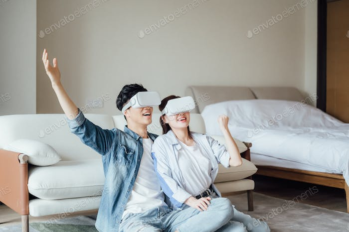 Young couple playing with VR glasses indoors