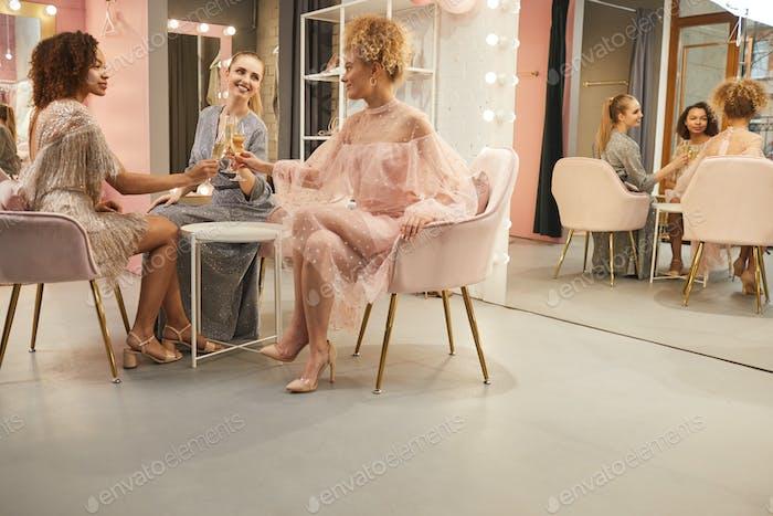 Beautiful Young Women Drinking Champagne in Showroom