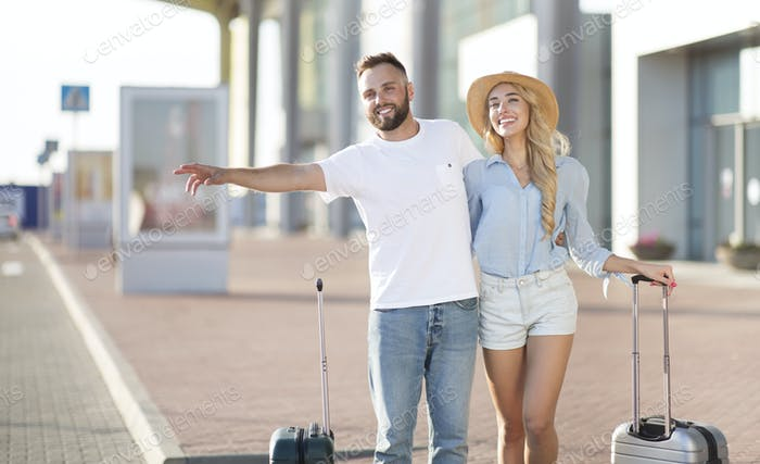 Young couple standing near airport trying to stop car