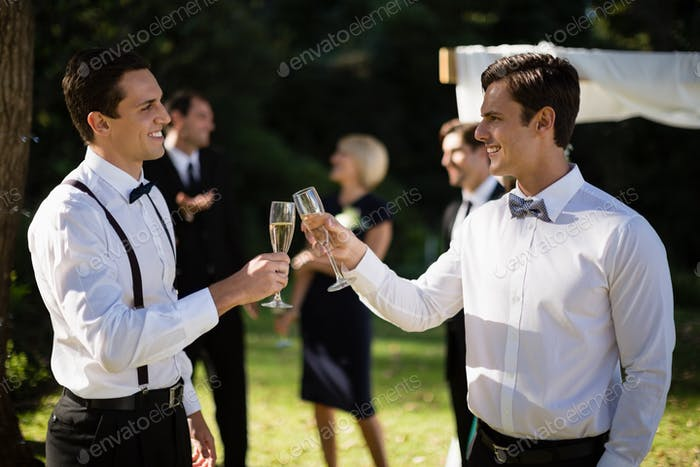 Waiters toasting champagne in park