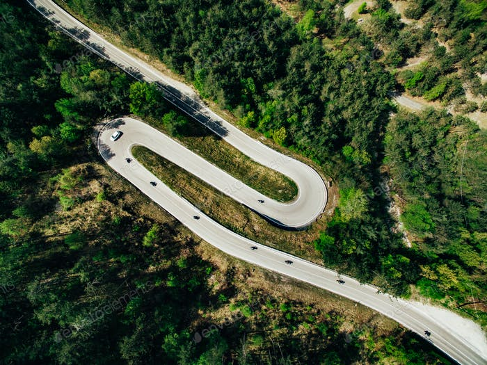Aerial above view of a rural mountain landscape with a curvy road in Italy.