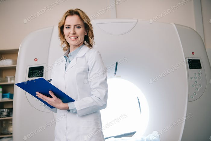 smiling radiologists writing on clipboard while standing near computed tomography scanner