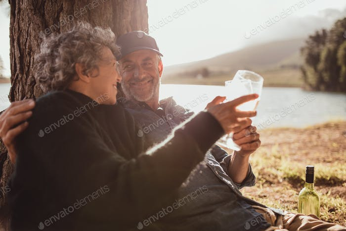 Senior couple enjoying camping near a lake