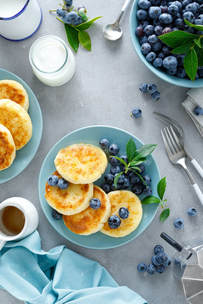 Cottage cheese pancakes, sweet curd fritters with berries, syrniki with honey and fresh blueberry
