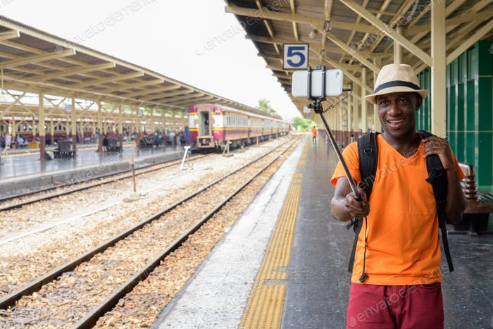 Young happy black African tourist man smiling and taking selfie